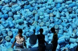 "Saudi boys sort through ""zamzam"" water containers at the Zamazemah United Office in Mecca. Nov. 7, 2010. According to Islamic belief, zamzam is a miraculously-generated source of water from God, which began thousands of years ago when Abraham's infant son Ishmael was thirsty and crying for water when it discovered a well by kicking the ground. Millions of pilgrims visit the well each year while performing the Hajj or Umrah pilgrimages, in order to drink its water. (Mustafa Ozer - AFP/Getty Images)"