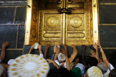 Muslim pilgrims reach to touch the golden doors of the Kaaba as they perform the walk around the Kaaba (Tawaf) at the Grand Mosque in the Saudi holy city of Mecca early morning. Nov. 9, 2010. (Mustafa Ozer - AFP/Getty Images)