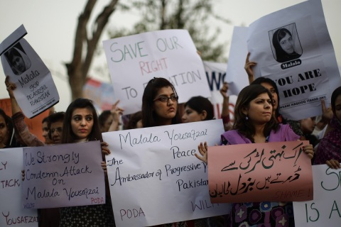 Pakistani women, hold banners during a protest condemning the attack on
