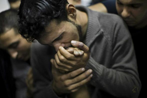 A Palestinian man kisses the hand of a dead relative in the morgue of Shifa Hospital in Gaza City, Sunday, Nov. 18, 2012. President Barack Obama on Sunday defended Israel's airstrikes on the Gaza Strip, but he warned that escalating the offensive with Israeli ground troops could deepen the death toll and undermine any hope of a peace process with the Palestinians. (AP Photo/Bernat Armangue)