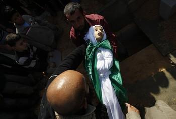 Nic6155249</p> <p>A Palestinian man barries the body of Tamer Abu Sefan, three and a half years old, during a funeral in the village of Beit Lahia, in the northern Gaza Strip on November 18, 2012. A ground invasion of the Gaza Strip would lose Israel much international sympathy and support, British Foreign Secretary William Hague warned. AFP PHOTO/MOHAMMED ABED (Photo credit should read MOHAMMED ABED/AFP/Getty Images) 2012 AFP