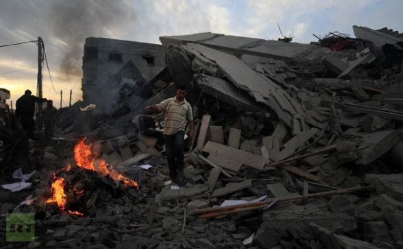 A Palestinian Hamas security member inspects the destroyed office building of Hamas Prime Minister Ismail Haniya in Gaza City on November 17, 2012 (AFP Photo / Mahmud Hams)