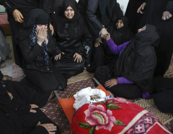 """Palestinian relatives of Samaher Gdeeh mourn next to her body during her funeral in Khan Younis in the southern Gaza Strip November 18, 2012. Israel bombed militant targets in Gaza for a fifth straight day on Sunday, launching aerial and naval attacks as its military prepared for a possible ground invasion, though Egypt saw """"some indications"""" of a truce ahead. REUTERS/Ibrahemm Abu Mustafa"""