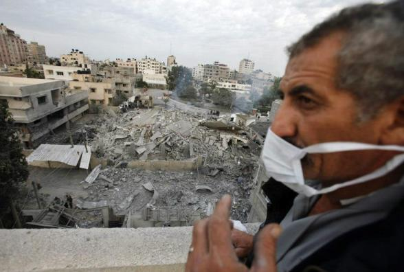 A Palestinian man stands near the destroyed office building of Prime Minister Ismail Haniyeh in Gaza City November 17, 2012. Israeli aircraft pounded Hamas government buildings in Gaza on Saturday, including the building housing the prime minister's office, after Israel's Cabinet authorised the mobilisation of up to 75,000 reservists, preparing the ground for a possible invasion into Gaza. REUTERS/Suhaib Salem