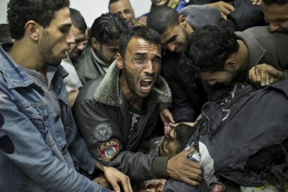 A Palestinian man cries next the body of a dead relative in the morgue of Shifa Hospital in Gaza City, Sunday, Nov. 18, 2012. President Barack Obama on Sunday defended Israel's airstrikes on the Gaza Strip, but he warned that escalating the offensive with Israeli ground troops could deepen the death toll and undermine any hope of a peace process with the Palestinians. (AP Photo/Bernat Armangue)