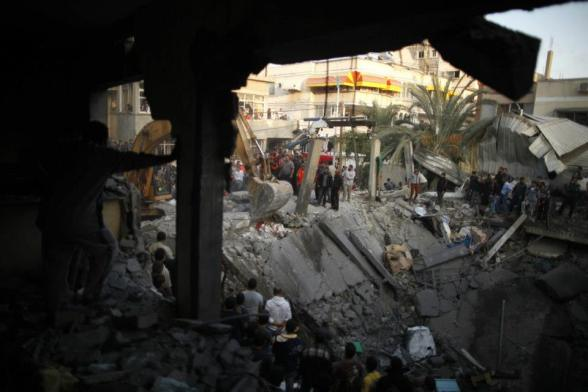 Palestinians gather around a destroyed house as members of civil defense search for victims under the rubble after an Israeli air strike in Gaza City November 18, 2012. Ten Palestinian civilians were killed on Sunday in an Israeli air strike on a house in Gaza, Palestinian medics said, the highest civilian death toll in a single incident during five days of fighting. REUTERS/Suhaib Salem (GAZA - Tags: MILITARY CONFLICT) — with Jessica Love.