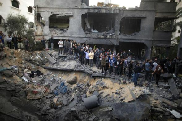 Palestinians gather around a destroyed house after an Israeli air strike in Gaza City November 18, 2012. Ten Palestinian civilians were killed on Sunday in an Israeli air strike on a house in Gaza, Palestinian medics said, the highest civilian death toll in a single incident during five days of fighting. REUTERS/Suhaib Salem