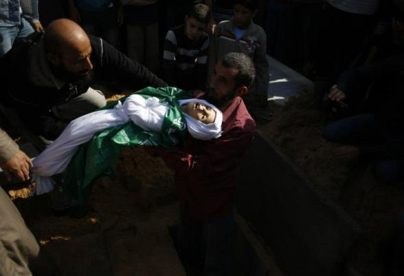 """A man buries a Palestinian child from Abu Sefan family at a cemetery in the northern Gaza Strip November 18, 2012. Two children Jumana Abu Sefan, 18 months old, and her brother Tamer, three and a half years old, were killed in an Israeli air strike on Sunday, hospital officials said. Israel bombed dozens of targets in Gaza for a fifth straight day on Sunday, launching aerial and naval attacks as its military prepared for a possible ground invasion, though Egypt saw """"some indications"""" of a truce ahead. REUTERS/Mohammed Salem (GAZA - Tags: CIVIL UNREST MILITARY POLITICS CONFLICT) — with Nikita Bukowski."""