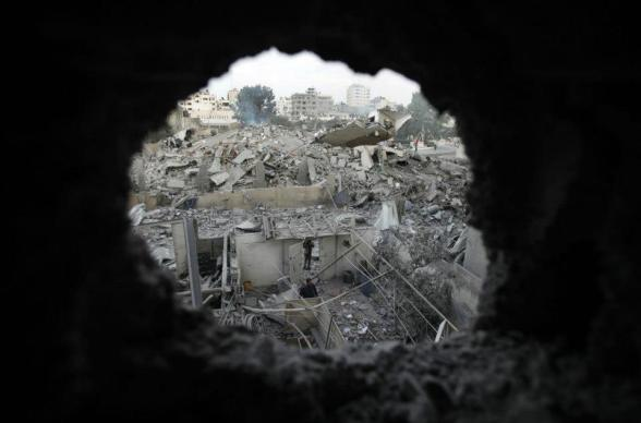 Palestinians are seen through a hole in the wreckage as they inspect the destroyed office building of Hamas Prime Minister Ismail Haniyeh in Gaza City November 17, 2012. Israeli aircraft pounded Hamas government buildings in Gaza on Saturday, including the building housing the prime minister's office, after Israel's Cabinet authorised the mobilisation of up to 75,000 reservists, preparing the ground for a possible invasion into Gaza. REUTERS/Suhaib Salem