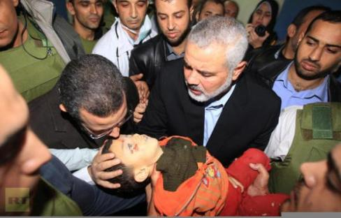 Hamas leader & Egypt PM hold body of Palestinian boy killed in Israeli air strike - Photo via @RT_com