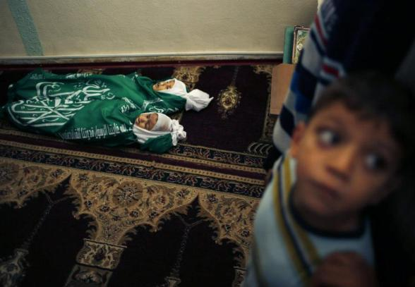 """A Palestinian boy stands next to the bodies of Jumana Abu Sefan, 18 months old, and her brother Tamer, three and a half years old, during their funeral at a mosque in the northern Gaza Strip November 18, 2012. The two siblings were killed in an Israeli air strike on Sunday, hospital officials said. Israel bombed militant targets in Gaza for a fifth straight day on Sunday, launching aerial and naval attacks as its military prepared for a possible ground invasion, though Egypt saw """"some indications"""" of a truce ahead. REUTERS/Mohammed Salem"""