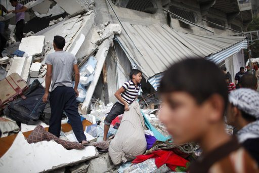 """Palestinians gather around a destroyed house after an Israeli air strike in Gaza City November 18, 2012. Israel bombed militant targets in Gaza for a fifth straight day on Sunday, launching aerial and naval attacks as its military prepared for a possible ground invasion, though Egypt saw """"some indications"""" of a truce ahead. REUTERS/Ahmed Jadallah"""