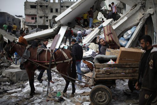 """Palestinians load their belongings onto a horse cart after an Israeli air strike on a house in Gaza City November 18, 2012. Israel bombed militant targets in Gaza for a fifth straight day on Sunday, launching aerial and naval attacks as its military prepared for a possible ground invasion, though Egypt saw """"some indications"""" of a truce ahead. REUTERS/Ahmed Jadallah"""