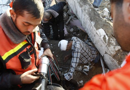 """Palestinian members of civil defense help evacuate a wounded man under the rubble of his house, after an Israeli air strike in Gaza City November 18, 2012. Israel bombed militant targets in Gaza for a fifth straight day on Sunday, launching aerial and naval attacks as its military prepared for a possible ground invasion, though Egypt saw """"some indications"""" of a truce ahead. REUTERS/Ahmed Zakot"""