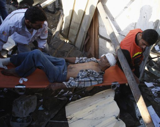 """Palestinians carry a wounded man after being evacuated from under the rubble of his house, following an Israeli air strike in Gaza City November 18, 2012. Israel bombed militant targets in Gaza for a fifth straight day on Sunday, launching aerial and naval attacks as its military prepared for a possible ground invasion, though Egypt saw """"some indications"""" of a truce ahead. REUTERS/Ahmed Zakot"""