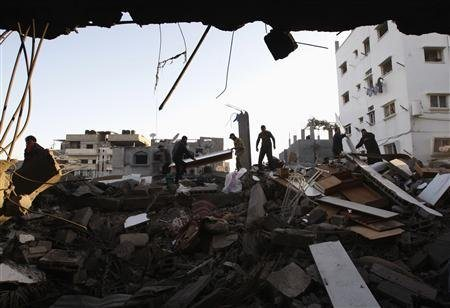 Palestinians inspect a destroyed house after an Israeli air strike in Gaza City November 18, 2012. REUTERS/Ahmed Zakot