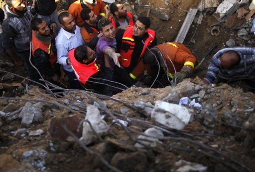 """Palestinian members of the Civil Defense help a survivor after he was pulled out from under the rubble of his destroyed house after an Israeli air strike in Gaza City November 18, 2012. Israel bombed militant targets in Gaza for a fifth straight day on Sunday, launching aerial and naval attacks as its military prepared for a possible ground invasion, though Egypt saw """"some indications"""" of a truce ahead. REUTERS/Suhaib Salem"""