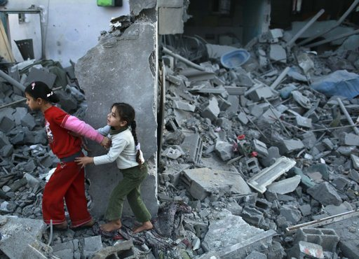 "Palestinian girls run away after an Israeli air strike on a house in the northern Gaza Strip November 18, 2012. Israel bombed militant targets in Gaza for a fifth straight day on Sunday, launching aerial and naval attacks as its military prepared for a possible ground invasion, though Egypt saw ""some indications"" of a truce ahead. REUTERS/Mohammed Salem"
