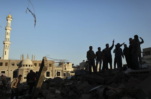 """Palestinians inspect a destroyed house after an Israeli air strike in the northern Gaza Strip November 18, 2012. Israel bombed militant targets in Gaza for a fifth straight day on Sunday, launching aerial and naval attacks as its military prepared for a possible ground invasion, though Egypt saw """"some indications"""" of a truce ahead. REUTERS/Mohammed Salem"""