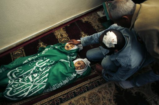 """A Palestinian man, father of Jumana Abu Sefan, 18 months old and her brother Tamer, three and a half years old, reacts next to their bodies during their funeral at a mosque in the northern Gaza Strip November 18, 2012. The two siblings were killed in an Israeli air strike on Sunday, hospital officials said. Israel bombed militant targets in Gaza for a fifth straight day on Sunday, launching aerial and naval attacks as its military prepared for a possible ground invasion, though Egypt saw """"some indications"""" of a truce ahead. REUTERS/Mohammed Salem"""