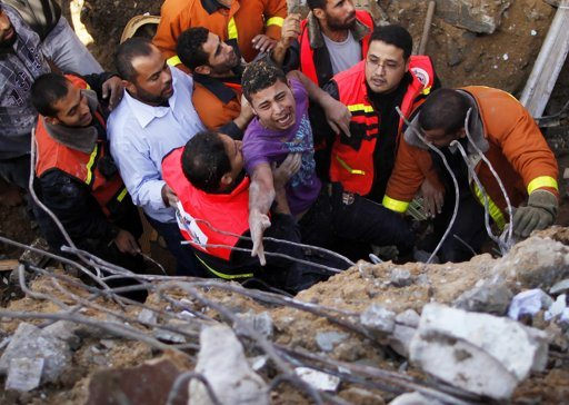"""Members of the Palestinian Civil Defense help a survivor after he was pulled out from under the rubble of his destroyed house after an Israeli air strike in Gaza City November 18, 2012. Israel bombed militant targets in Gaza for a fifth straight day on Sunday, launching aerial and naval attacks as its military prepared for a possible ground invasion, though Egypt saw """"some indications"""" of a truce ahead. REUTERS/Suhaib Salem"""