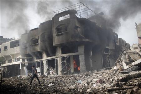 A Palestinian walks past a burning house after an Israeli air strike in Gaza City November 18, 2012. REUTERS/Ahmed Jadallah