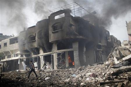A Palestinian walks past a burning house after an Israeli air strike in Gaza City November 18, 2012. REUTERS/Ahmed Jadallah