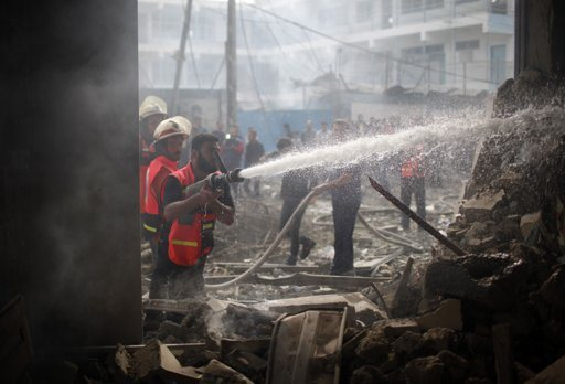"""Palestinian firefighters extinguish a fire after an Israeli air strike on a house in Gaza City November 18, 2012. Israel bombed militant targets in Gaza for a fifth straight day on Sunday, launching aerial and naval attacks as its military prepared for a possible ground invasion, though Egypt saw """"some indications"""" of a truce ahead. REUTERS/Ahmed Jadallah"""