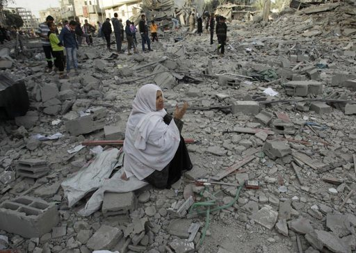 """A Palestinian woman reacts as she sits on the rubble of her destroyed house after an Israeli air strike in Rafah in southern Gaza Strip November 18, 2012. Israel bombed militant targets in Gaza for a fifth straight day on Sunday, launching aerial and naval attacks as its military prepared for a possible ground invasion, though Egypt saw """"some indications"""" of a truce ahead. REUTERS/Ibrahemm Abu Mustafa"""