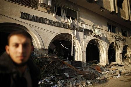 A Palestinian walks past the Islamic National Bank after it was destroyed in what witnesses said was an Israeli air strike in Gaza City November 20, 2012. International pressure for a ceasefire in the Gaza Strip puts Egypt's new Islamist president in the spotlight on Tuesday after a sixth day of Palestinian rocket fire and Israeli air strikes that have killed over 100 people. REUTERS/Suhaib Salem
