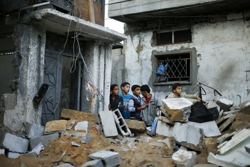 Palestinian boys stand next to the destroyed house of Hejazi family after what Hamas Health Ministry said was an Israeli air strike in the northern Gaza Strip November 20, 2012. Four members of the same Hejazi family - four-year-old twin boys and their parents - were killed in the Israeli air strike in Gaza on Monday, the Hamas Health Ministry said. Israel had no immediate comment on the attack, one of more than 80 bombings during the day in the Hamas-ruled territory, where Israel launched an aerial offensive on Wednesday it says is intended to quell rocket fire at its cities. REUTERS/Suhaib Salem