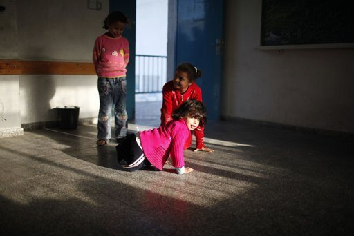 Displaced Palestinians, who fled their houses, sit in a classroom as they stay at a United Nations-run school in Gaza City November 20, 2012. From the sandy expanses of the northern Gaza Strip, Palestinian families are fleeing their homes destroyed by airstrikes, but refuse to blame the Hamas rocket crews who draw Israeli fire. REUTERS/Ahmed Jadallah