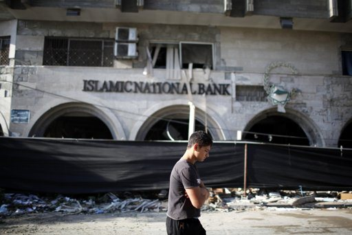 Palestinians look at the Islamic National Bank after it was destroyed in what witnesses said was an Israeli air strike in Gaza City November 20, 2012. International pressure for a ceasefire in the Gaza Strip puts Egypt's new Islamist president in the spotlight on Tuesday after a sixth day of Palestinian rocket fire and Israeli air strikes that have killed over 100 people. REUTERS/Ahmed Jadallah