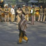 A woman walks past police officers standing guard in front of a closed road leading to the India Gate in New Delhi December 29, 2012. An Indian woman whose gang rape in New Delhi triggered violent protests died of her injuries on Saturday in a Singapore hospital, bringing a security lockdown in Delhi and recognition from India's prime minister that social change is needed. The India Gate has been the epicenter of previous related protests. REUTERS/Ahmad Masood (INDIA - Tags: CIVIL UNREST CRIME LAW)