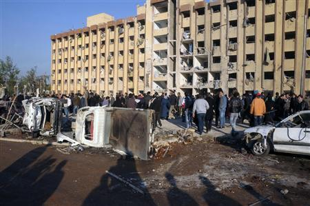 Syrian security personnel and civilians gather at the site where two explosions rocked the University of Aleppo in Syria's second largest city, January 15, 2013. REUTERS/George Ourfalian (SYRIA - Tags: POLITICS CIVIL UNREST)
