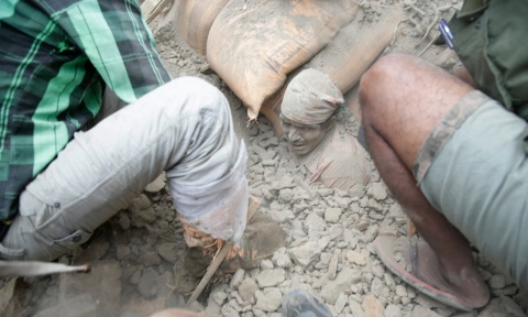 People try to free a man from the rubble of a destroyed building in Kathmandu