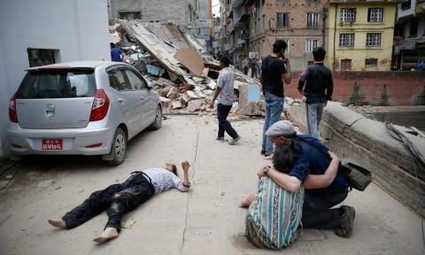 A man comforts a woman next to a seriously injured person on the ground after the earthquake