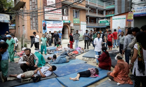 Health workers take care of injured people outside the Manmohan Memorial community hospital after an earthquake caused serious damage in Kathmandu, Nepal