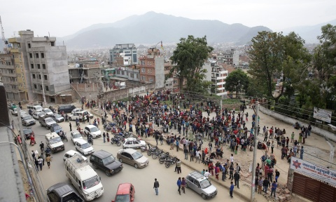 Citizens gather outside on a public square after an earthquake caused serious damage in Kathmandu