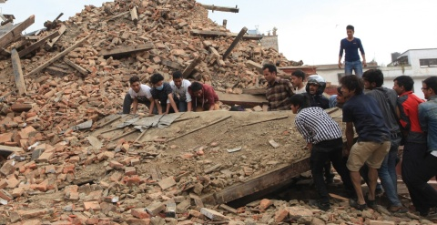 People try to lift the debris from a temple at Hanumandhoka Durbar Square after the earthquake in Kathmandu