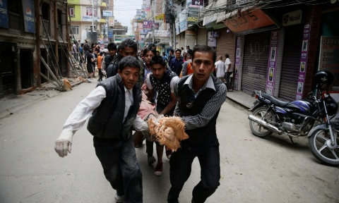 A group of men carry an injured person through the street after an earthquake caused serious damage in Kathmandu