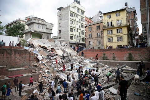 People search for survivors stuck under the rubble of a destroyed building in Kathmandu