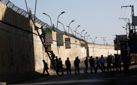 Palestinians who had been prevented from crossing into Jerusalem through the Kalandia checkpoint use a ladder to climb over the wall in al-Ram town