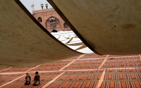 Indian Muslim boys pray in the compound of Jama Masjid on the first day of Ramadan in New Delhi, India