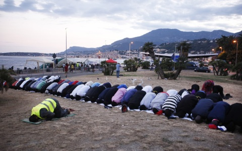 Migrants pray for the start of Ramadan as they wait to cross the French border from Italy in Ventimiglia, Italy
