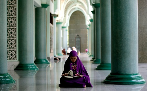 A Muslim woman reads the Koran during the first day of the fasting month of Ramadan at a Mosque on the outskirts of Jakarta, Indonesia