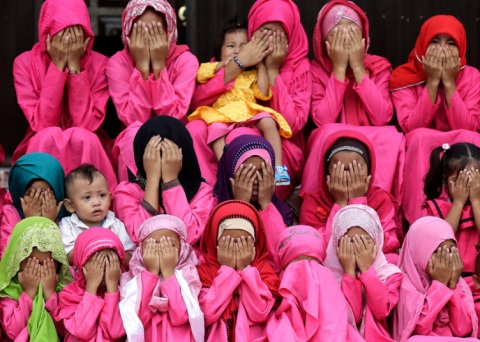 Filipino Muslim children are taught by an Arabic teacher the proper way of praying on the first day of the holy fasting month of Ramadan, outside the Pink mosque in Datu Saudi Ampatuan town, southern Philippines