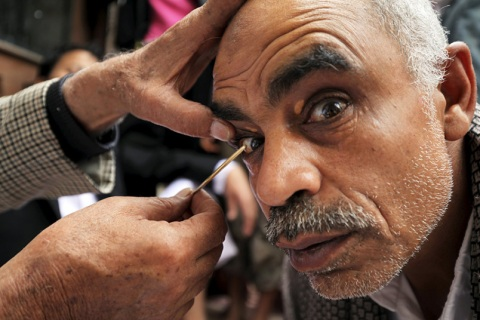 A man gets kohl applied to his eyelids at the Grand Mosque during the holy fasting month of Ramadan in Sanaa, Yemen. The cosmetic powder is traditionally popular in Yemen as a protection against eye ailments.
