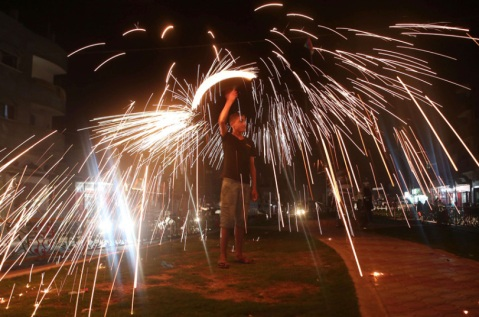A Palestinian boy celebrates with fireworks during the Muslim holy month of Ramadan, in Rafah, in the southern Gaza Strip