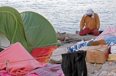 A migrant prays on the rocky beach at the Franco-Italian border in Ventimiglia, Italy